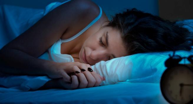 Woman sleeping in a bed in a dark bedroom in hindi